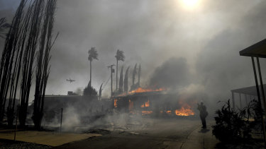 Firefighters battle the Sandalwood Fire as it destroys homes in the Villa Calimesa Mobile Home Park in Calimesa, California.