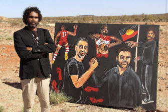 Artist Vincent Namatjira with his Archibald Prize-winning portrait of himself and Adam Goodes.