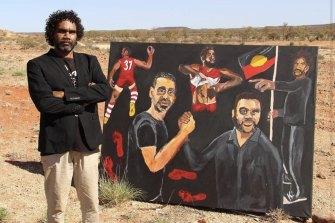 Vincent Namatjira with his 2020 Archibald Prize-winning portrait of Adam Goodes.