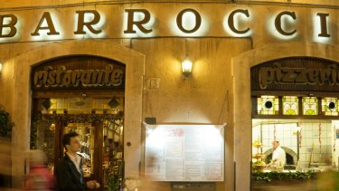 People walk by the Barroccio restaurant in Rome, a trattoria raided in 2017 as an alleged fronts for money-laundering operations for the `ndrangheta.