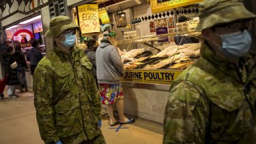 Members of Victoria Police aided by ADF soldiers patrol the Queen Victoria Market.