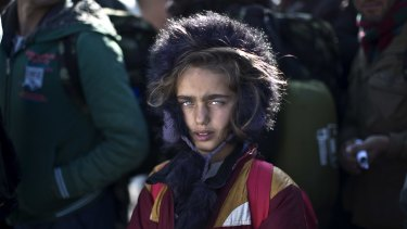 Yazidi refugee Salma Bakir, 9, from Iraq, waits with her family to be permitted by Macedonian police to board a train heading to the Serbian border.