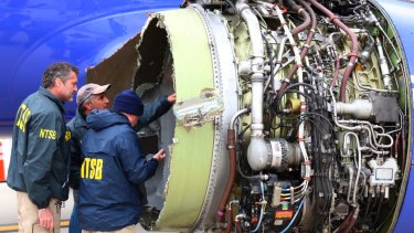Investigators examine damage to the engine of the Southwest Airlines plane that made an emergency landing in Philadelphia in April.