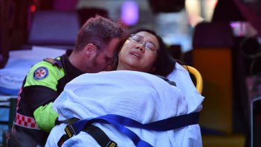 The woman who was stabbed outside Hotel CBD is taken away in an ambulance.