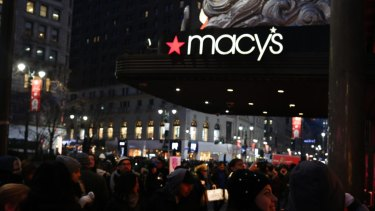 Pedestrians pass in front of a Macy's Inc. department store in New York, US,