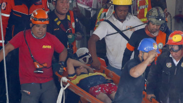 Rescuers carry an earthquake survivor after being pulled out from the rubble of a supermarket following a 6.1 magnitude earthquake in Porac township, Pampanga, north of Manila.