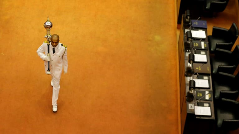 Sri Lanka's sergeant at arms Narendra Fernando walks carrying the mace in the well of the house past empty seats of President Maithripala Sirisena and disputed Prime Minister Mahinda Rajapaksa at the beginning of the parliamentary session in Colombo, Sri Lanka.