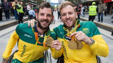 Heath Davidson and Dylan Alcott during a city parade after the 2016 Paralympics.
