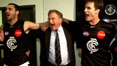 Carlton president John Elliott enjoys a win with players in 2002.