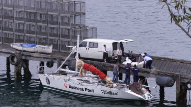 Police remove the bodies of two crewmen from the Business Post Naiad which was towed into Eden.