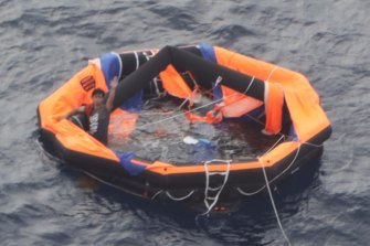 The 30-year-old can be seen on the left of the life raft waving for help.