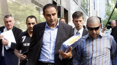 Rob Karam (centre) carrying a blue folder, outside Melbourne Magistrates Court in 2009.