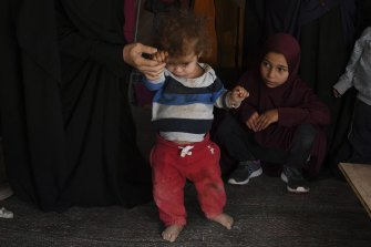 Australian women and children watch as Omeid, aged 1 yr and 7 months, is assisted in walking in al-Hawl camp.