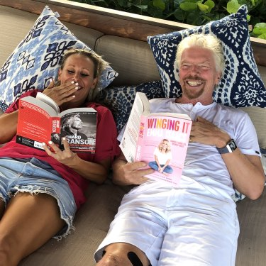 Isaacs and her mentor, British billionaire Richard Branson, enjoy each other's book while intheCaribbean.