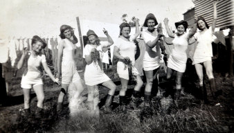Necia Combe (second from left) with a colander on her head enjoying the company of other Land Army women.
