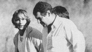 Detectives escort Gary Murphy to paddock where Anita Cobby was murdered.