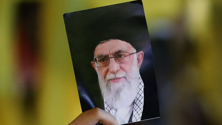 A Hezbollah supporter holds a portrait of Iran's supreme Leader Ayatollah Ali Khamenei.