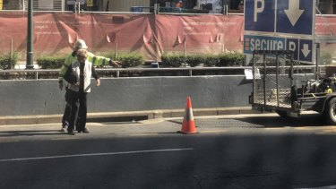 A traffic controller points an older woman to walk down Adelaide Street.