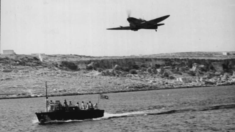 A Spitfire flies over the Malta-based high-speed launch during the war.