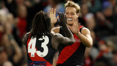 Anthony McDonald-Tipungwuti and Darcy Parish celebrate a goal during the Bombers' clash with the Dockers  at Marvel Stadium.