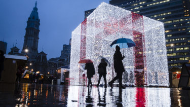 People walk on a rainy evening by The Present in the Christmas Village at John F. Kennedy Plaza, commonly known as Love Park, in Philadelphia, Thursday, Dec. 20, 2018.