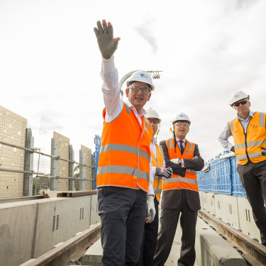 "Andrews visits the partly constructed Noble Park ""sky rail"" overpass in 2018. Tackling the traffic bottlenecks created by rail-and-road intersections this way has been popular with the electorate."