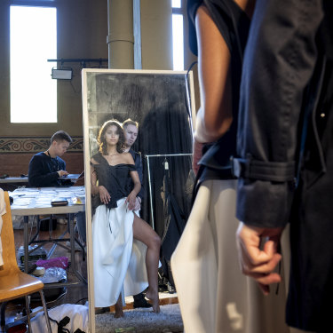 Toni Maticevski adjusts a dress during a fitting for his show.