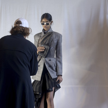 Stylist Jolyon Mason locks in a look with a photograph of the model.