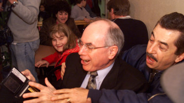 PM John Howard tries to pay for his first GST coffee at the Rendezvous Coffee House shop on July 1, 2000.