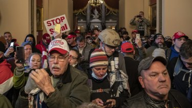 Demonstrators walk through the US Capitol after breaching barricades to the building.