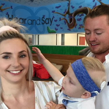 Rome Whelan, 18 months, is seen with his mother Renae Whelan and father Ryan Walker, celebrating his new cochlear implant.