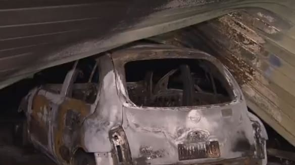 Stolen car rammed into Brisbane business before being set alight, police allege