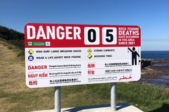 A new warning sign at Hill 60 where five men died rock fishing this year. Lifesaver Anthony Turner was involved in finding two men who died after being swept off the rocks.