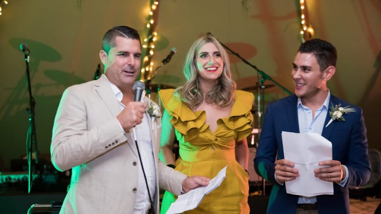 Corinne Mulholland (centre) was MC at the wedding of Shane Newcombe (left) and Ethan Tyler (right).
