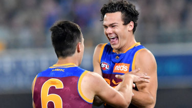 Hugh McCluggage (left) of the Lions celebrates kicking a goal with Cam Rayner (right).