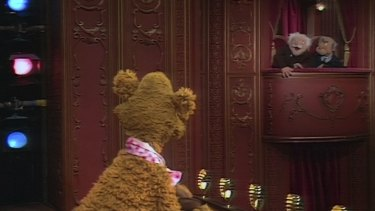 Statler and Waldorf heckle Fozzie Bear on stage in The Muppet Show.