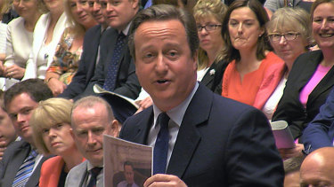 David Cameron displays a photo of himself and Larry the government's  Chief Mouser during a lighthearted final session of prime minister's questions before he resigned.