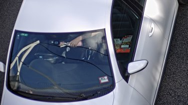 A man prepares to inhale nitrous oxide while speeding down the highway.