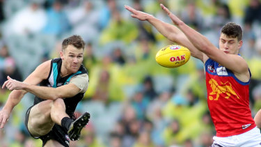 Spoiler: Oscar McInerney smothers a kick from Port's Robbie Gray.