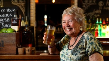 Merle Thornton, who chained herself to the bar at the Regatta Hotel on March 31, 1965, poses with a pint of beer at the same bar 50 years on in March 2015.