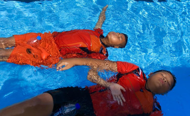 Children practise floating at a pool in Surat Thani using a second hand water bottle as a flotation device.