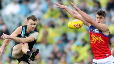 Spoiler: Oscar McInerney smothers a kick from Port's Robbie Gray.