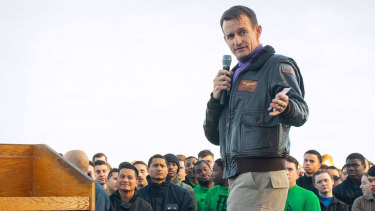 Captain Brett Crozier, commanding officer of the aircraft carrier USS Theodore Roosevelt gives remarks during an all-hands call on the flight deck in December.