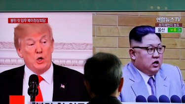 A man watches a TV screen showing file footage of US President Donald Trump, left, and North Korean leader Kim Jong-un, in Seoul.