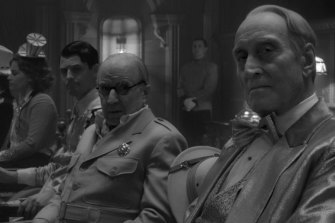 "Arliss Howard, centre, and Charles Dance, right, appear in a scene from ""Mank""."