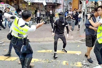The video captures the moment a Hong Kong policeman holds onto one protester and shoots a second protester, who was later hospitalised.