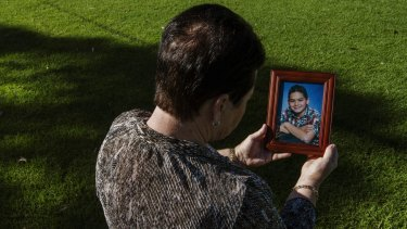 Mohammed Noor Masri's mother holds a photo of her son taken in 2002.