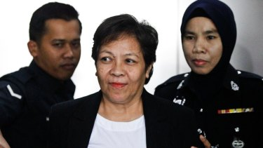 Australian Maria Elvira Pinto Exposto, centre, is escorted during a court hearing in Shah Alam, Malaysia, in 2017.