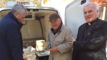 Monsignor Konrad Krajewski, right, stands with a cheese maker in Camerino, central Italy.