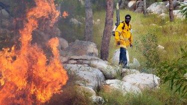 An Indigenous rangers controls a wildfire in Kakadu.
